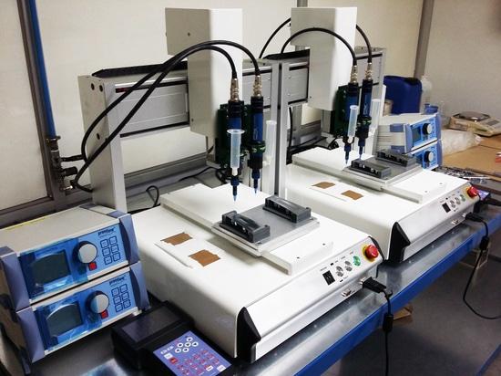 preeflow eco-PEN300 Dosificador de 1 componente y controlador de dosificación eco-CONTROL EC200-K en un sistema de dosificación para la aplicación de laca en emblemas.
