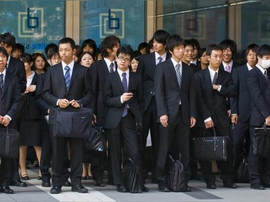 Tokio , Japón - 29 de octubre de 2009: Empleados de oficina japoneses en el exterior de un edificio de oficinas en el distrito financiero de Tokio, Japón